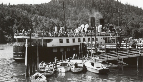 A large steamer, with smoke coming out of the smokestack, tuba-shaped ventilation funnels, small pleasure boats moored at small docks in front.