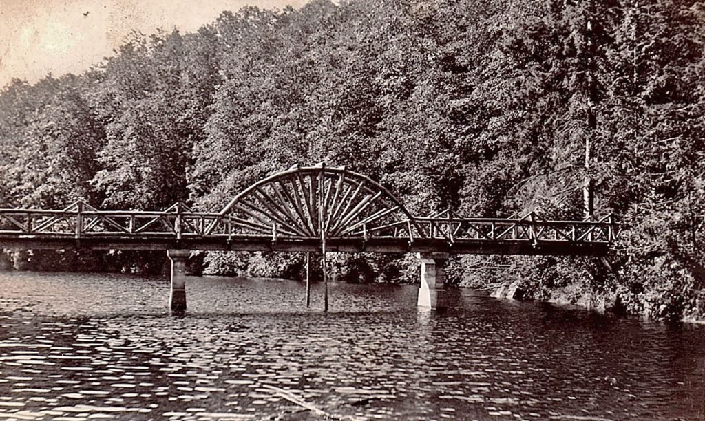 A wooden bridge across the middle of the lagoon with spoked arches in the middle like giant half wagon wheels