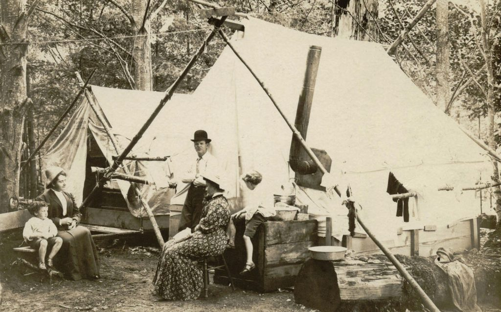 An a-frame canvas tent, an outdoor wooden stove, a man in a bwler hat and woman in early 20th century dress in the woods on Bowen Island BC