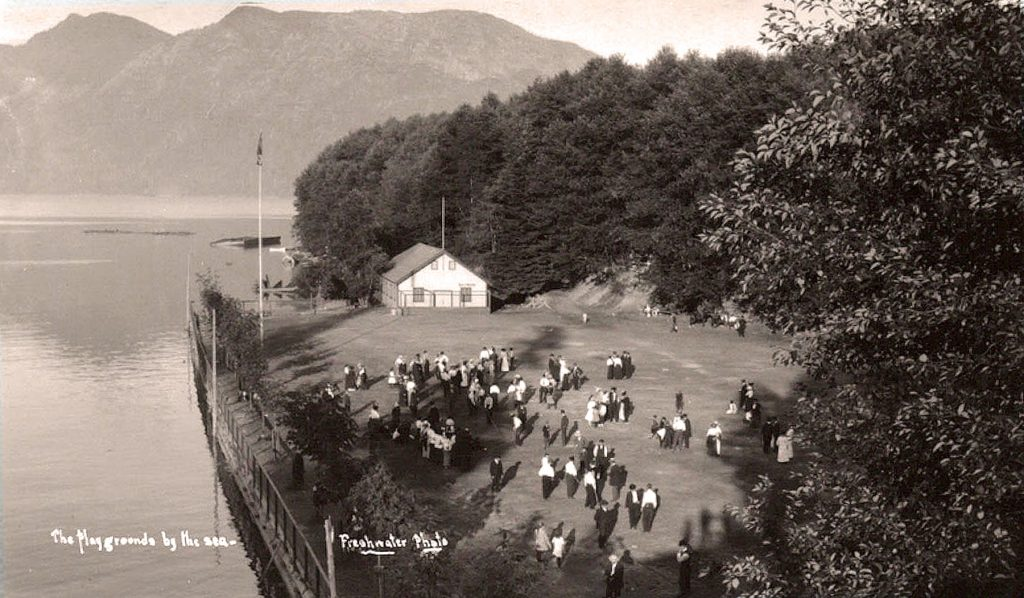 A group of people on the picnic grounds - actually used more as a playing field, with the dancehall in the background and Sandy Beach behind it.