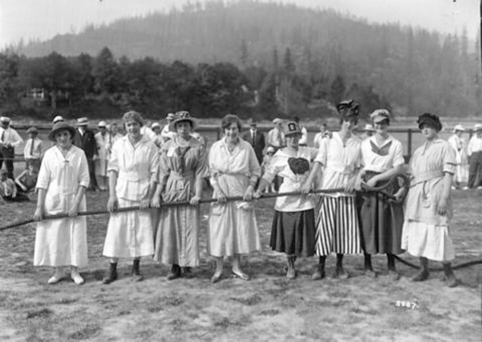 A group of women in old fahsioned white dresses gamely hold the end of a thick tug of war rope.