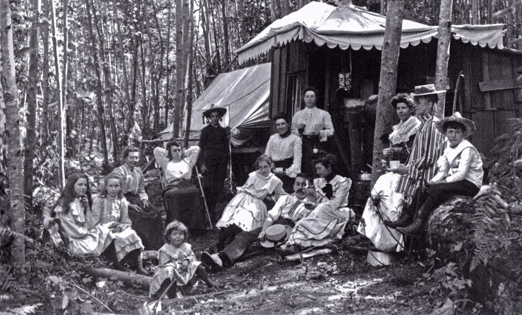 A group of Edwardian men and women sit stiffly in a big group including kids beside a fancy tent