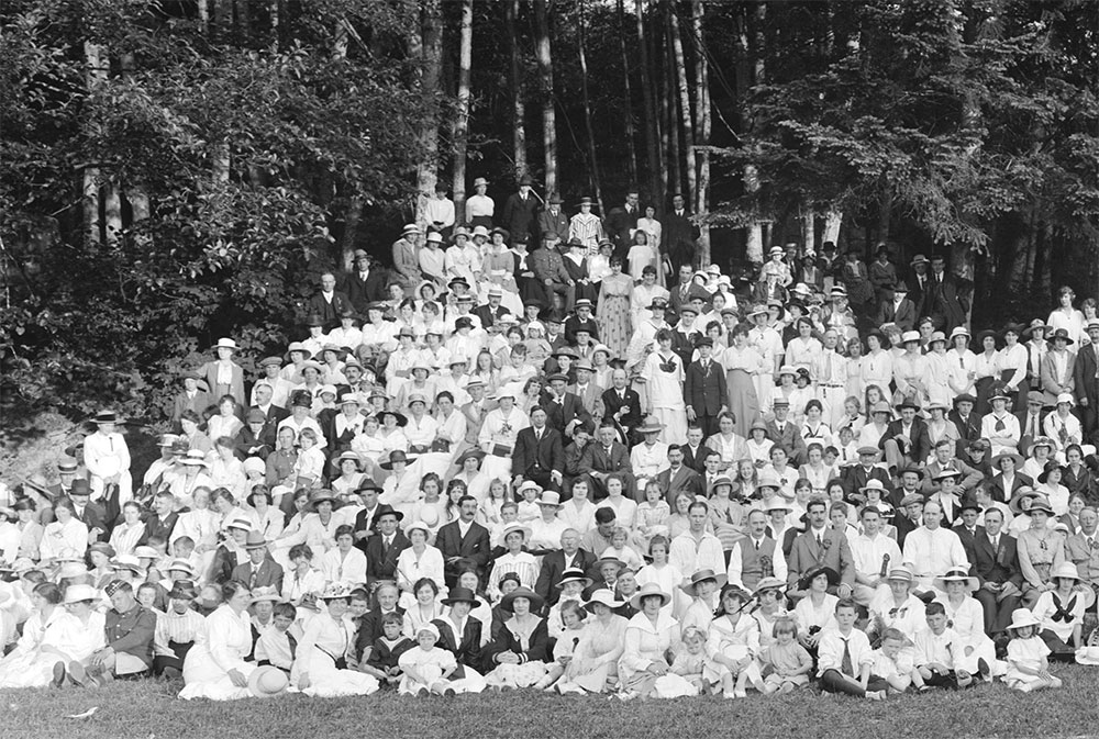 over one hundred people in formal wear posed in a dozen rows in front of the rainforest on Bowen Island BC