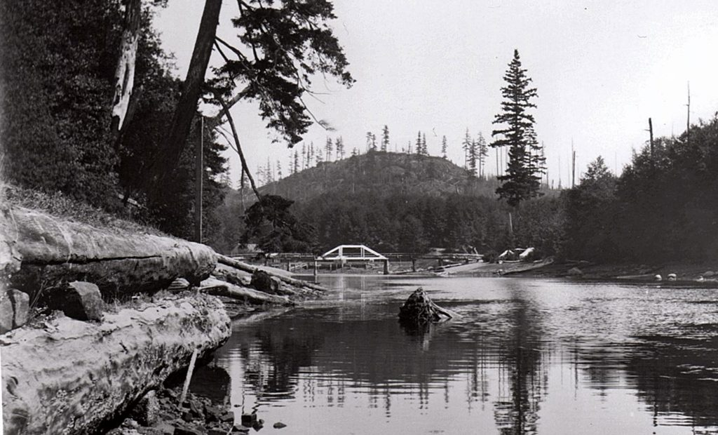 The bridge from the side, with a logged mountain with staggered lone trees.