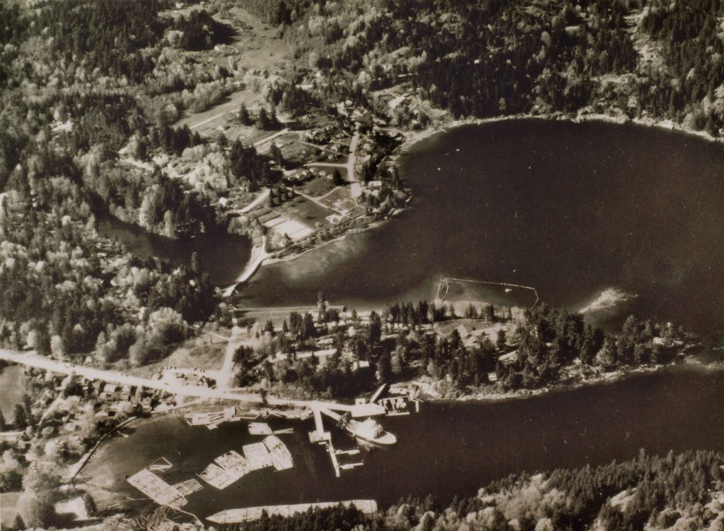Aerial photo of Snug Cove in the thirties showing resort and log booms